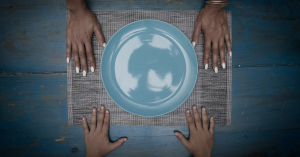 Adult's and child's hands with empty blue plate between them.